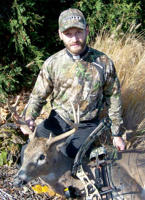 Fr. Ken, bow hunting priest with harvested buck