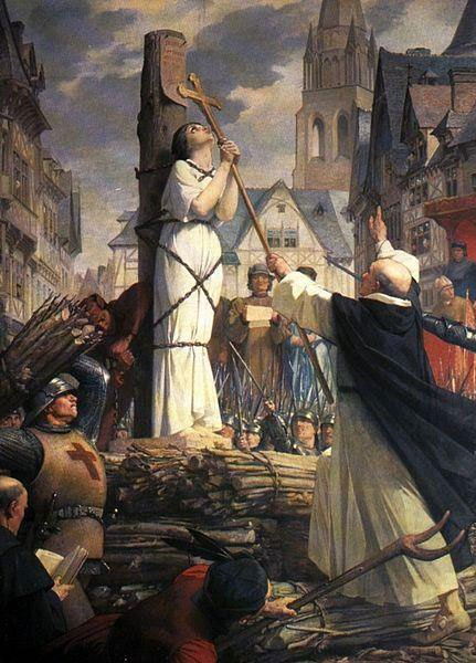 Joan of Arc kissing the cross before being burned at the stake